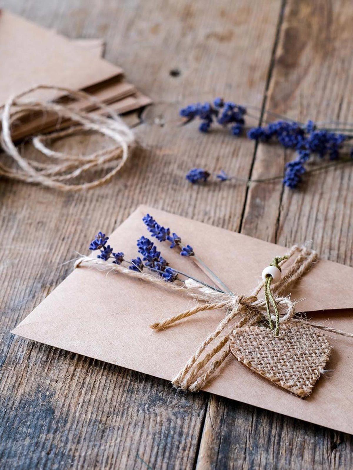 Ein Geschenk-Gutschein ist in einen Umschlag verpackt, der mit einem Anhänger und Lavendel zugebunden wurde, auch im Hintergrund liegen Briefe und Lavendel