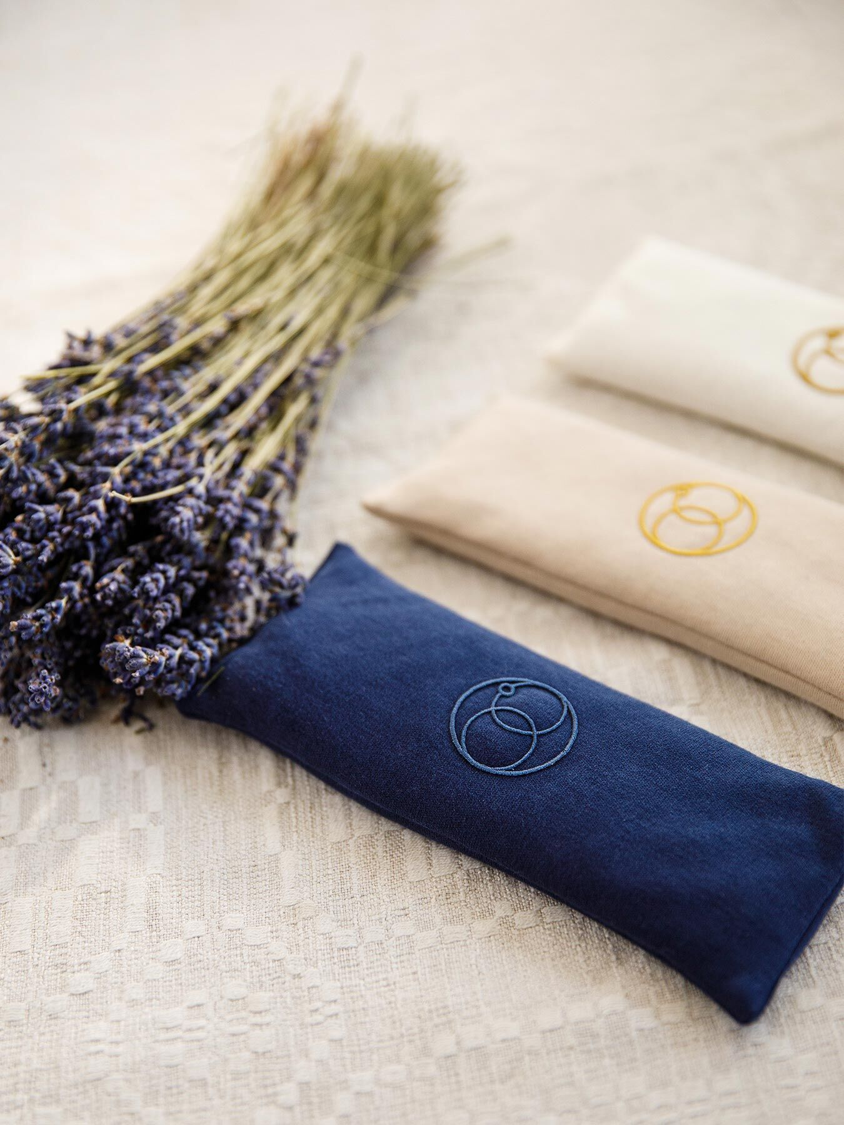 Die Entspannungs-Augenkissen in weiß, beige und blau neben einem Strauß Lavendel