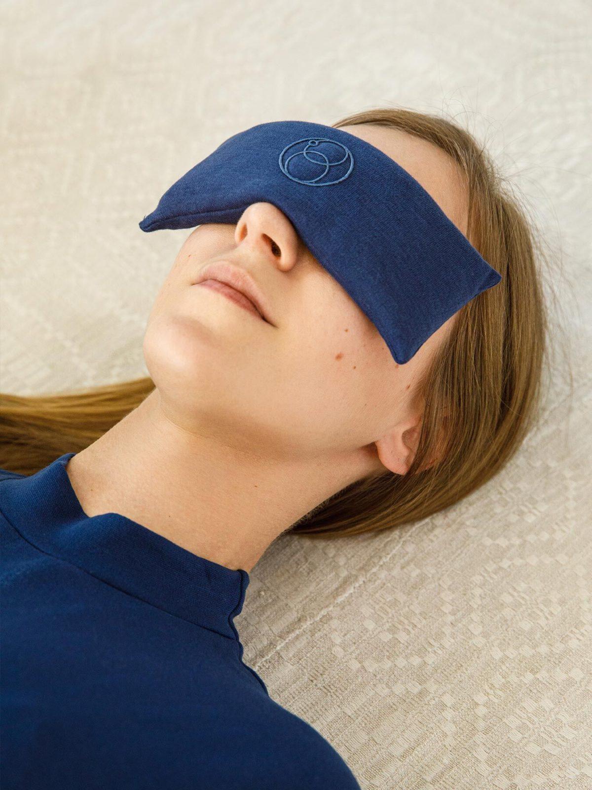 Das Entspannungs-Augenkissen in blau liegt auf den Augen eines ModelsModel