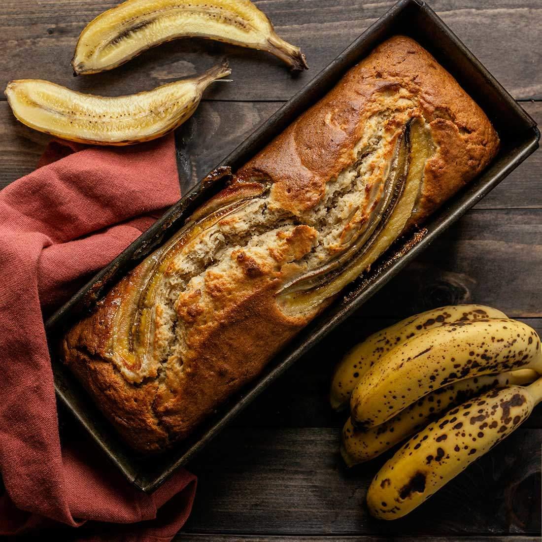 In einer Kuchenform ist ein Mandel-Kokos-Bananenbrot, daneben liegen reife Bananen als Ei-Alternative