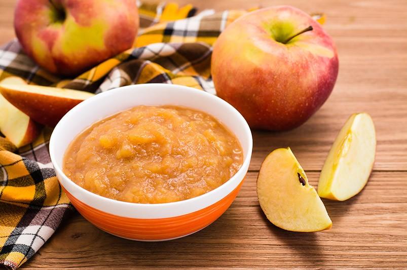 Neben einer Schüssel mit Apfelmus liegen Äpfel. Apfelmus ist eine tolle Ei-Alternative