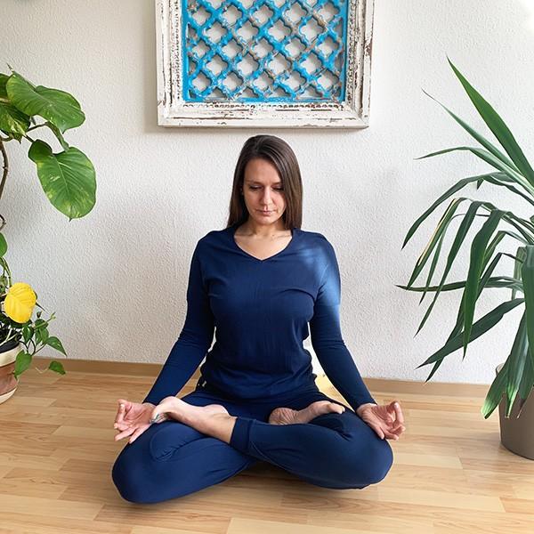 Yogini sitzt im Lotussitz und meditiert, sie trägt des Yoga Longsleeve Matangi und die Hose Tara in Marine