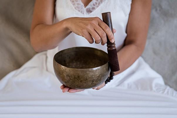 Eine Frau hält eine Klangschale in ihren Händen und übt Klangmeditation