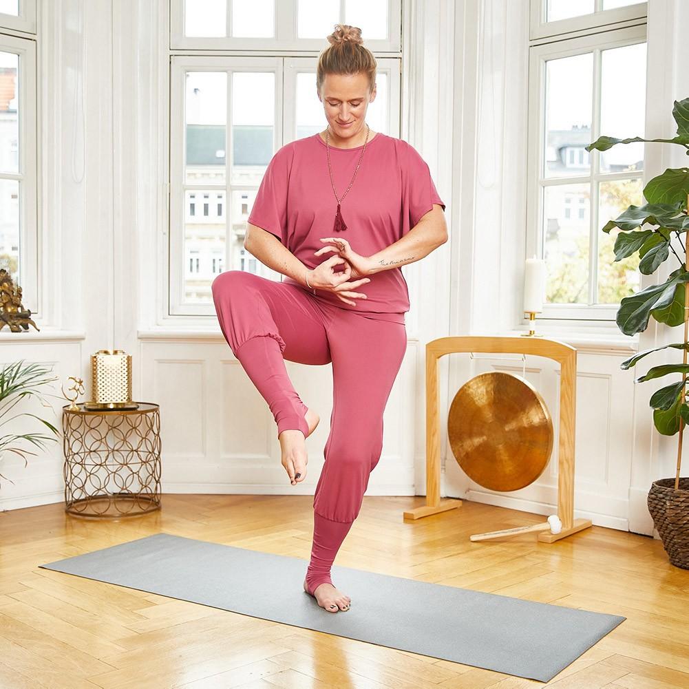 Frau steht in einer Yogapose, formt Mudras und trägt dabei eine Mala und die Stulpenhose Lakshmi