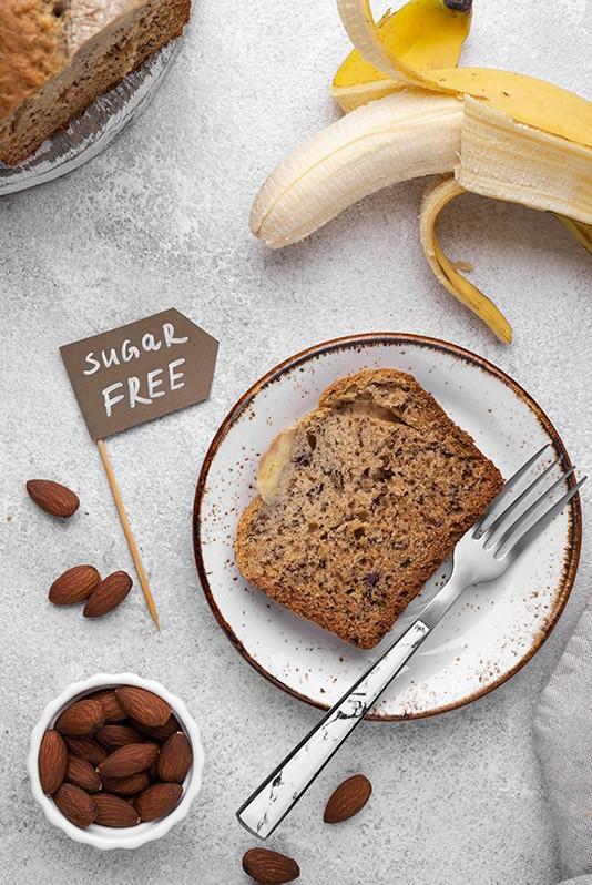 Das Mandel-Kokos-Bananenbrot wurde in Scheiben geschnitten, es ist Zuckerfrei, daneben liegt eine Banane und eine Schüssel mit Mandeln