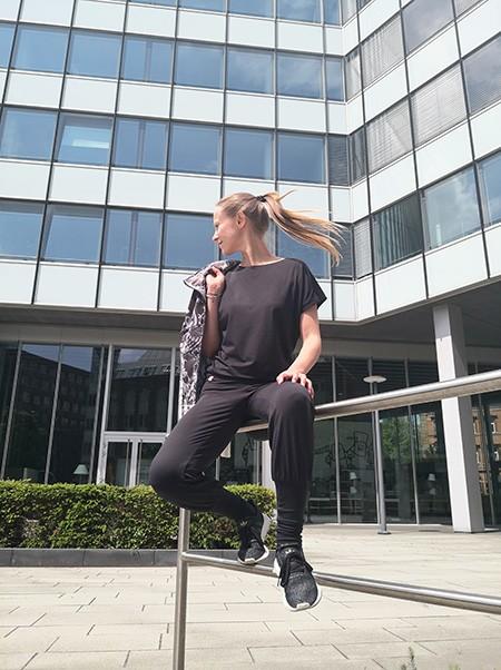 Frau sitzt auf einem Geländer und trägt eine schwarze Yoga-Hose und ein schwarzes Yoga Oberteil aus ihrer Capsule Wardrobe kombiniert mit einer sportlichen Jacke und Sneaker