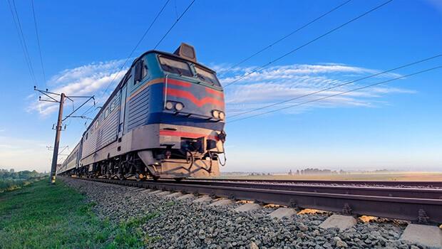 Im Urlaub mit der Bahn verreisen, eine Bahn fährt auf den Gleisen in einer schönen Landschaft, der Himmel ist blau