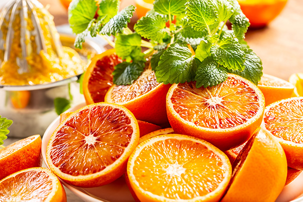 mehrere halbierte Orangen liegen auf einem Brett, daneben ist ein Büschel Zitronenmelisse