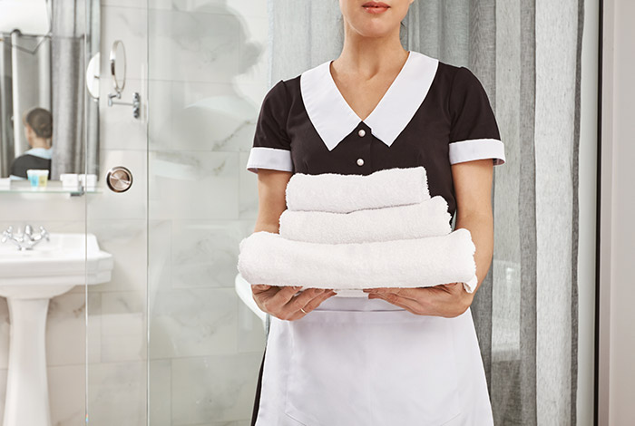 Urlaub im Hotel, Bedienstete trägt saubere Handtücher