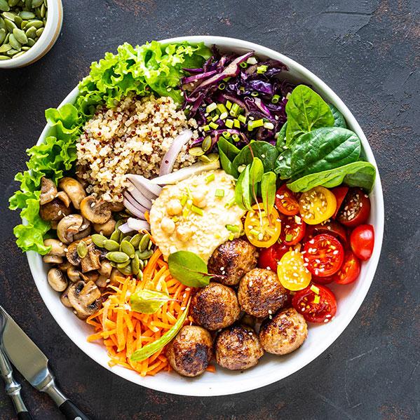 Eine Bowl ist gefüllt mit buntem Gemüse und Hackbällchen.