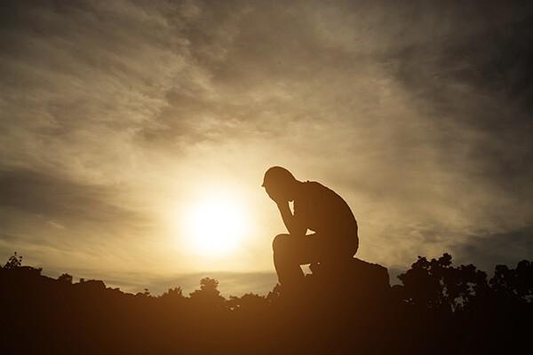 Eine Person sitzt rechts auf einem großen Stein. Sie stützt den Kopf auf die Hände, während die Sonne aufgeht.
