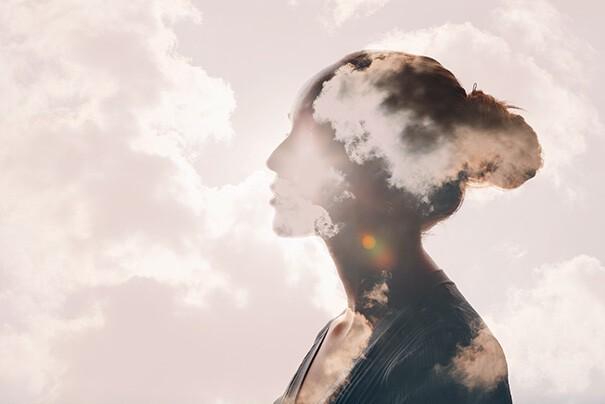 Das Seitenprofil einer Frau ist zu sehen. Durch sie hindurch sind Wolken zu sehen.