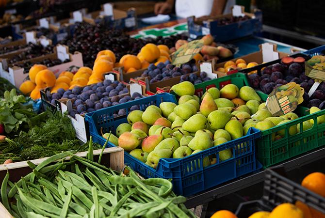 Verschiedene s Obst liegt in Kästen nebeneinander bei einem Marktstand.