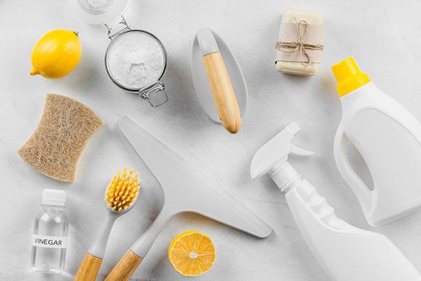 Verschiedene Behälter für Reinigungsmittel, Bürsten und Schwämme sowie zwei Zitronen liegen auf einer sauberen weißen Fläche.