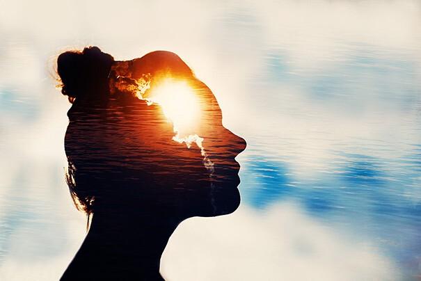 Das Profil einer Frau ist zu sehen. Ihr Kopf scheint transparent und zeigt die Sonne im Himmel.