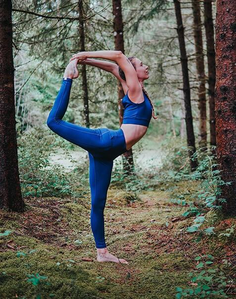 Eine Frau führt im Wald eine Yogapose aus. Sie trägt die Active-leggings-Shakti und das raffinierte Bustier Sundari.