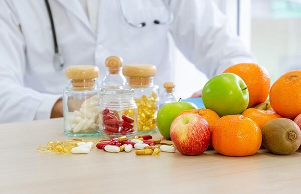 Vor einem Tisch sitzt eine Person in einem weißen Arztkittel. Auf dem Tisch liegen Obst und verschiedene Vitamine und Nahrungsergänzungsmittel.